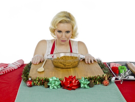 christmas paste: Young woman looking at paste of christmas cookies against white background  Stock Photo