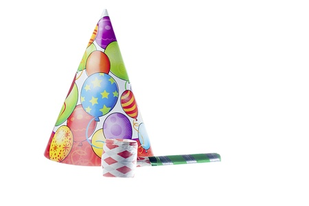 Close-up shot of colorful party hat with balloon design and whistle against white background.