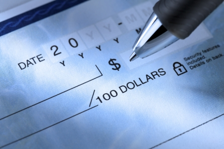 writing western: Extreme close-up image of a ballpoint pen and a cheque.