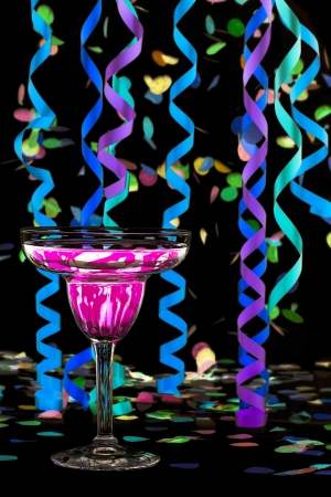 Close-up shot of martini with pink drink and colorful streamers and confetti over dark background. Stock Photo - 16995060