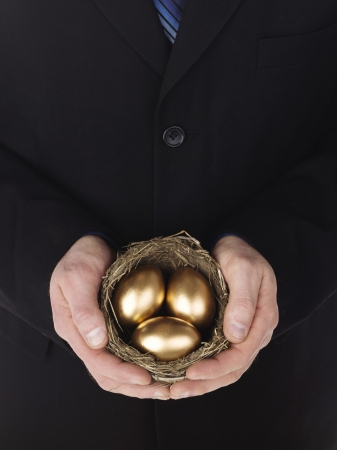 Close-up shot of a businessman holding golden eggs in nest. Model: Winter Bourne photo