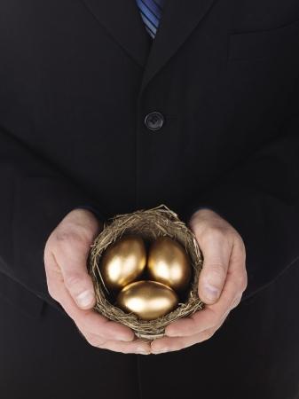 huevos de oro: Primer plano de un hombre de negocios la celebraci�n de los huevos de oro en el nido. Modelo: Winter Bourne