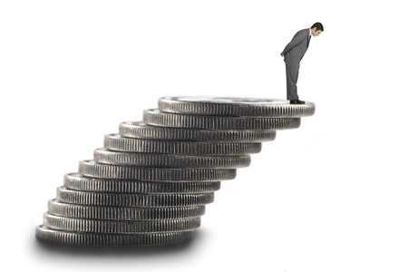 Digital image of a businessman standing on top of stack of coins.