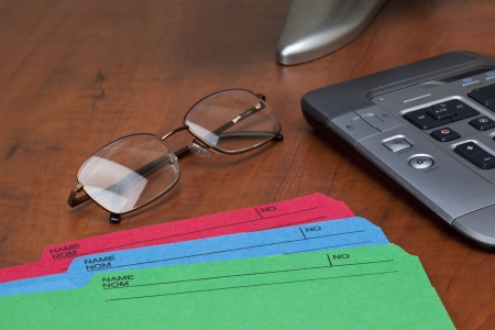 A horizontal image of wooden office table with folder, keyboard and spectacles Stock Photo - 16973220