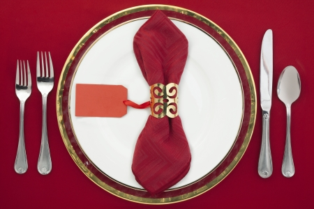 Table setting with plate, silverware and red napkin photo