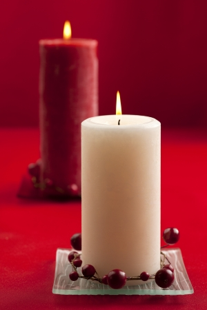 Close-up shot of white candle decorated with fake red berries and red candle in background. photo