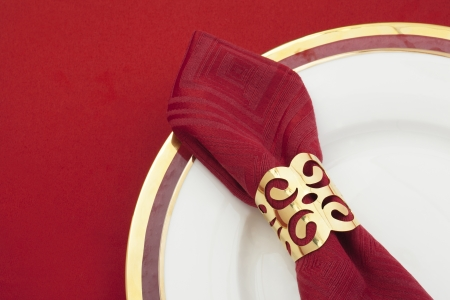 Close up image of red table napkin on a plate on red background Stock Photo