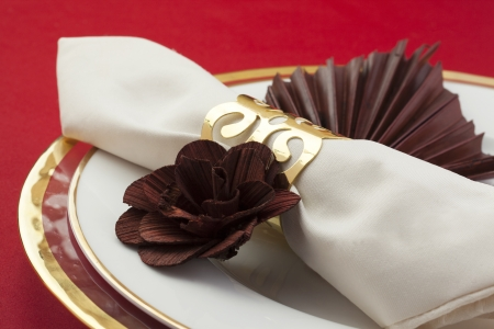 banqueting: Close up image of white table napkin white flower decoration on white plate on red background