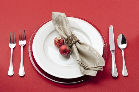 Close-up shot of a table covered with red table cloth with plate, forks and Christmas bulb. Stock Photo - 16973044