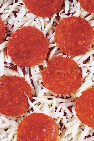 Overhead shot of a pepperoni pizza with ham slices and cheese topping.