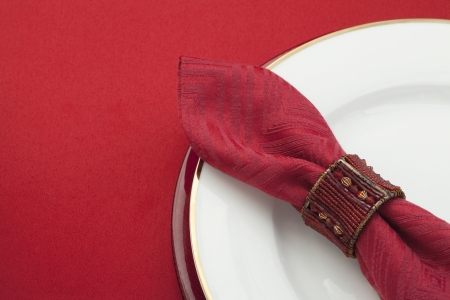 banqueting: Cropped image of white plate with a red ring napkin isolated Stock Photo