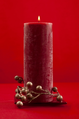 Red candle and berries on a red background photo
