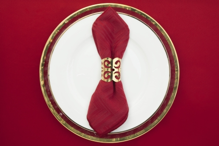 napkin ring: Red sating napkin with napkin ring on a ceramic plate Stock Photo