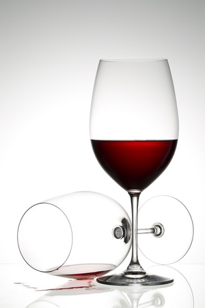 Empty and wine glass goblet with red wine on a grey background