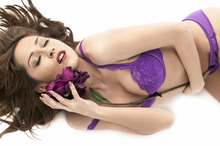semi nude: A close up image of a sensual woman lying on a white background and hugging a stem of purple flower