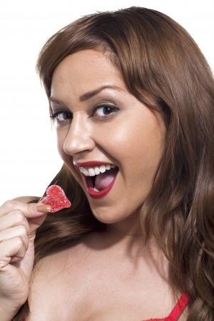 Portrait of a gorgeous young woman eating heart shape candy photo