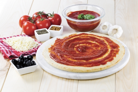 tomato paste: Tomato paste spread on raw pizza dough with grated cheese, black olives, tomato sauce and tomato