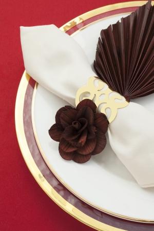 napkin ring: Golden napkin ring with white satin napkin on a plate Stock Photo