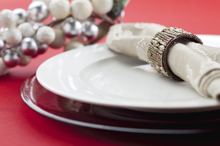banqueting: A close-up shot of a white plate and a table napkin on a red table background Stock Photo