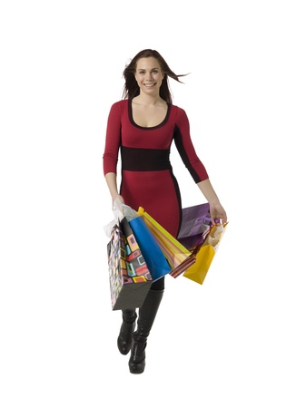 shoppingbags: Portrait of a cheerful female carrying her shopping bags as she walks over a white background