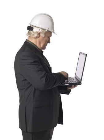 Portrait of old architect holding a laptop against white background
