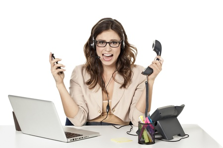 Portrait of a businesswoman holding a phone and cellphone and screaming in great stressed