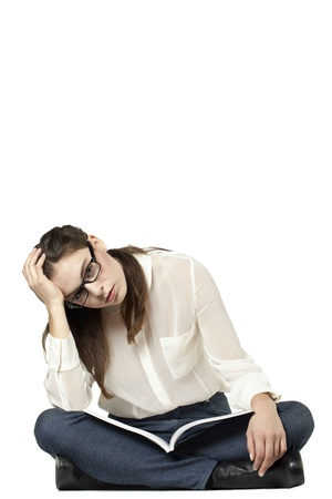 Portrait of a stressed female sitting in a white background with book on her lap Stock Photo - 16993090
