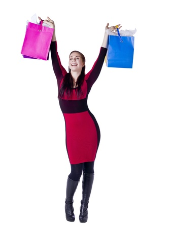 Young woman lifting her hands with shopping bags photo