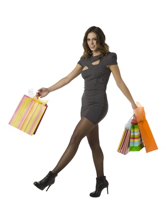 shoppingbags: Woman shopper carrying her shopping bags as she steps joyfully over a white background