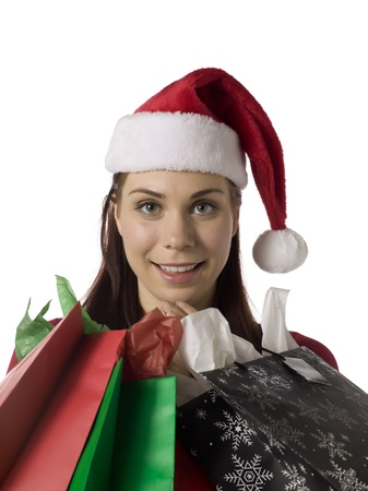 Image of woman wearing santa hat with shopping paper bags against white background photo