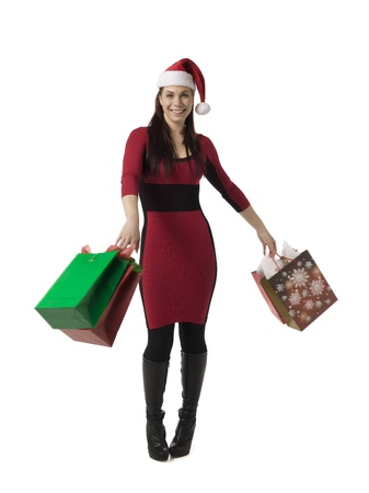 Young woman wearing santa hat and carrying shopping bags with Christmas presents photo