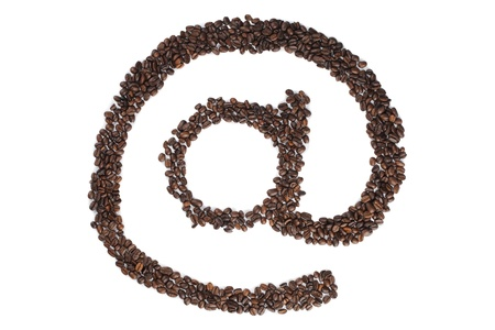 caffeine molecule: Close-up shot of coffee beans arranged to form @ symbol on white surface.