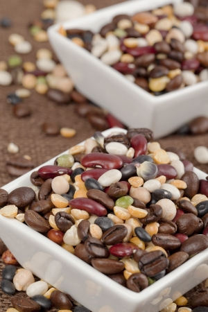 cropped image: Cropped image of two white bowl with scattered assorted beans on the table