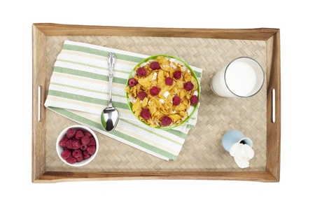 Top view shot of a wooden tray with cereals, glass of milk, raspberries, napkin, spoon, and base with a white flower Stock Photo - 16997164