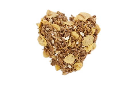 scattered in heart shaped: Close up image of a cereal on a heart shaped against white background