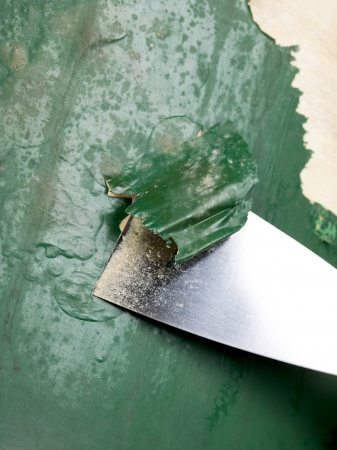 Close-up image of a chisel scraping paint on the old chair