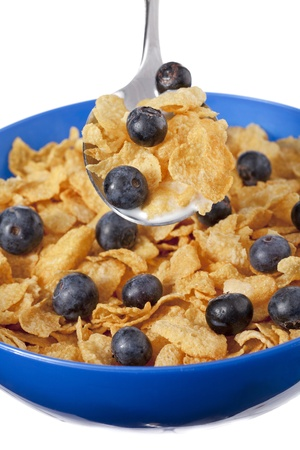 Close-up image of cornflakes with blueberries and milk inside the blue bowl photo