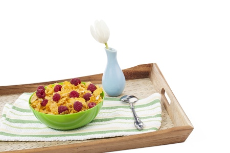corn flower: An image of a corn flakes bowl on a wooden tray together with a spoon, table napkin and awhite flower on a vase