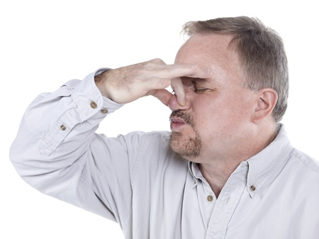 pungency: Portrait of an old man holding his nose tight to plug out the horrible smell Stock Photo