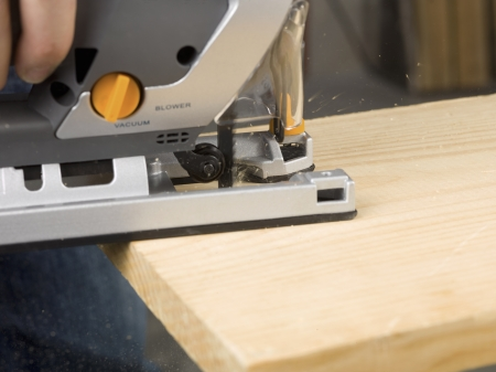 Close-up image of hand holding an electric jigsaw cutting the plank Stock Photo - 16998986