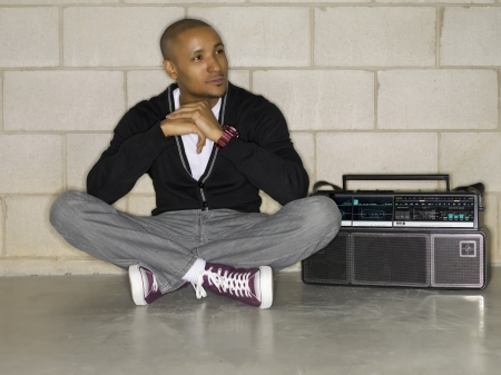 Image of a guy sitting beside a boom box Stock Photo - 17071081