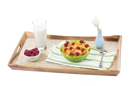 Image of a wooden tray with a bowl of cereals, raspberries, glass of milk, napkin, spoon and a flower inside a blue base isolated in a white background Stock Photo - 16998988