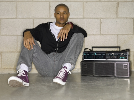 Image of a hip hop African man sitting on the floor beside his stereo photo