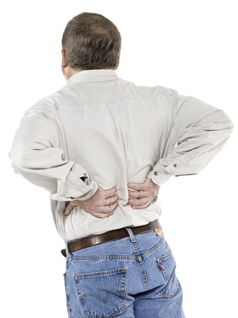 Senior man with hands on the back rubbing his lower back muscles that is in pain photo