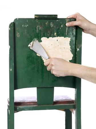 silla de madera: Quite la pintura de una silla de madera con la paleta con la mano