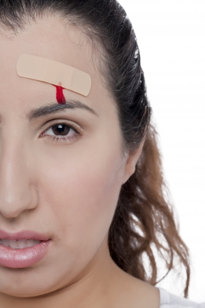 Cropped image of a wounded woman with a bandage on the forehead in a white surface photo