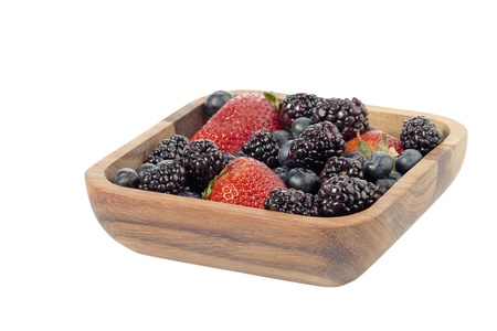 Image of a wooden bowl with strawberry, blackberry and blueberry on a white background