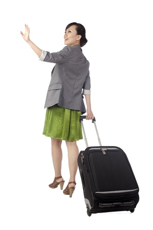 Back view of a female traveler holding her luggage gesturing goodbye photo
