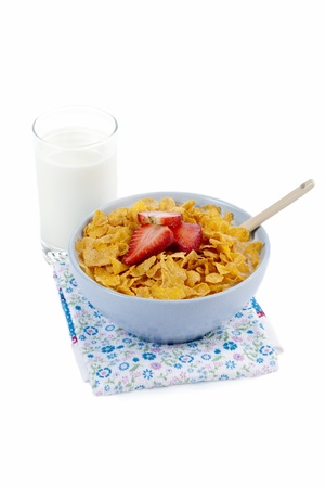 Bowl of cereals with strawberry slices on top served together with a glass of milk, spoon and floral napkin Stock Photo - 16997992