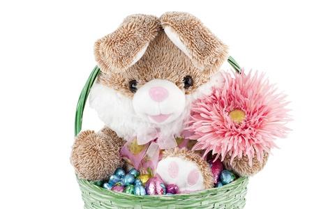 oeufs en chocolat: Tir fa�ade d'un jouet lapin mignon trucs tenant une fleur assis dans un panier vert plein d'oeufs en chocolat